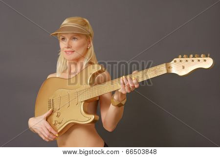 Woman With Blonde Hair wearing a visor Holding big gold Guitar.