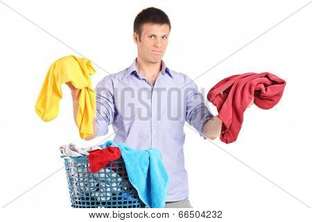 Indecisive man holding two sweaters isolated on white background