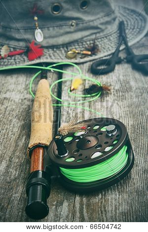 Fly-fishing reel with old hat and equipment on bench