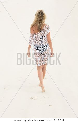 Rear view of blonde woman in walking on the beach