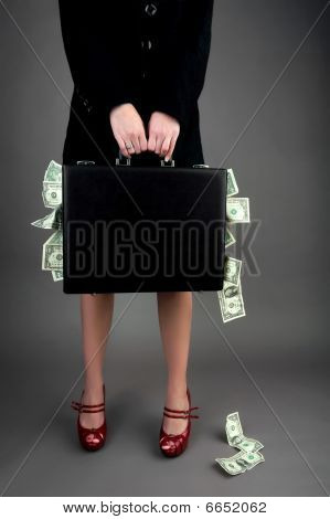 Woman Holding Briefcase Overflowing With Money