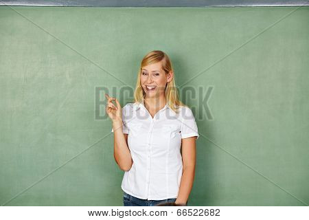 Happy smiling woman pointing on empty chalkboard in school