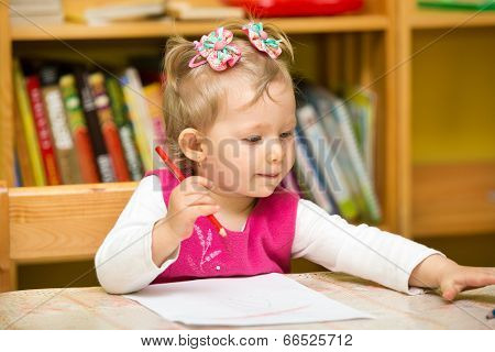 Child Girl Drawing With Colorful Pencils In Preschool At The Table. Little Girl And Boy Drawing In K