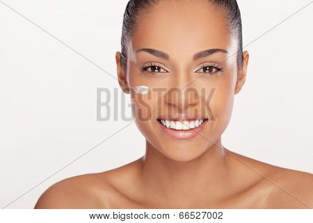 Close-up portrait of a beautiful smiling african woman with cream on her face