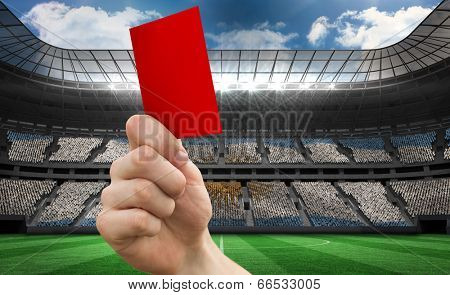 Hand holding up red card against stadium full of argentina football fans