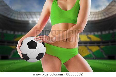 Fit girl in green bikini holding football against large football stadium with brasilian fans