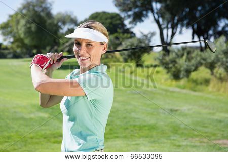 Female golfer taking a shot and smiling at camera on a sunny day at the golf course
