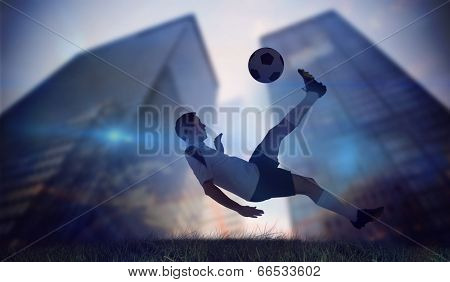 Football player in white kicking against low angle view of skyscrapers