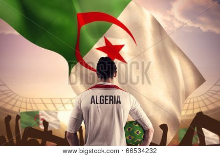 Algeria football player holding ball against large football stadium under bright blue sky