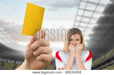 Hand holding up yellow card against football stadium with fan