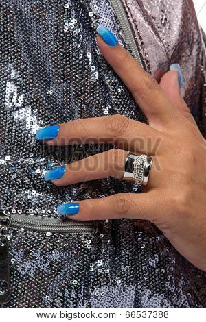 closeup of the woman's hand wearing luxury ring, blue gradient nail art manicure on silver sequin material background