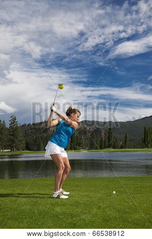 Outdoor photo of attractive woman golfing.