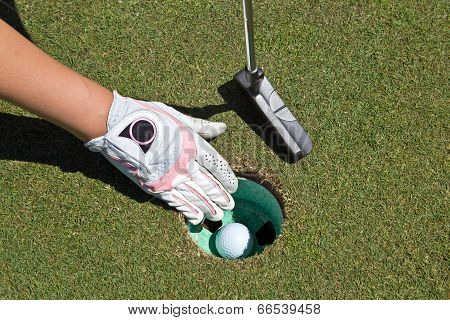 Woman's Gloved Hand, Putter And Golf Ball In The Cup