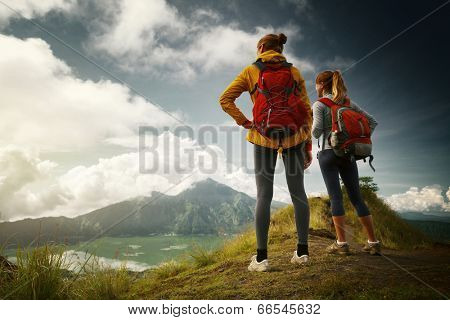 Two hikers standing on top of the mountain and enjoying view