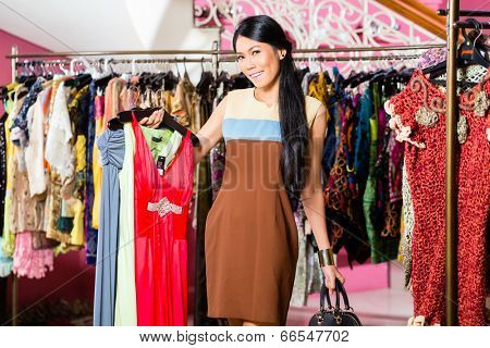 Asian young woman choosing garment in fashion store
