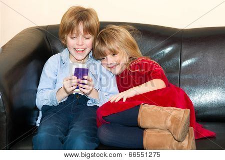 Two Young Children Playing With A Mobile Phone