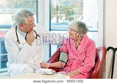 Doctor Taking An Elderly Womans Blood Pressure