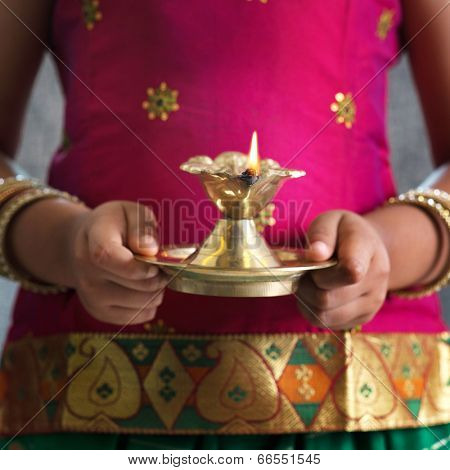 Diwali or deepavali photo with female hands holding oil lamp during festival of light.