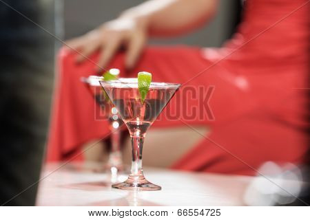 Close up of woman in red dress with cocktail in hands