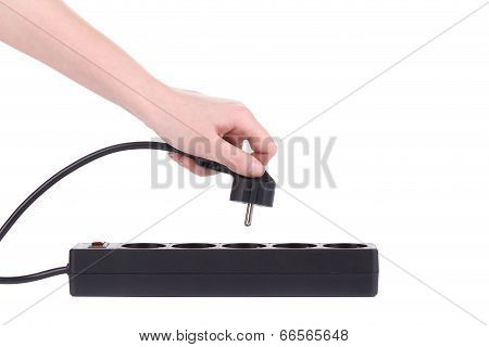 Hand puts the plug in an extension cord