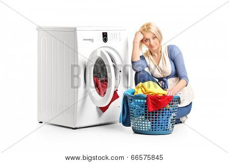 Bored woman sitting by a washing machine and doing laundry isolated on white background
