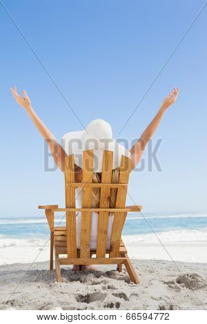Woman sitting in deck chair at the beach with arms up on a sunny day