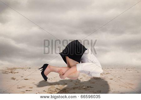 Businesswoman burying her head against misty desert landscape