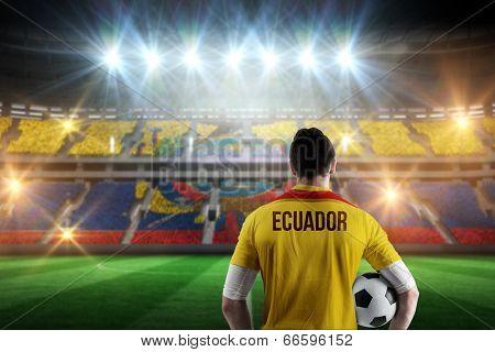 Ecuador football player holding ball against stadium full of ecuador football fans