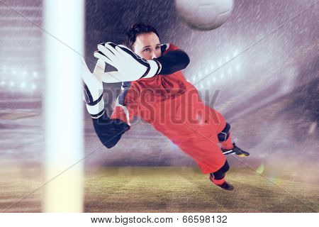 Fit goal keeper jumping up against football stadium