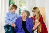 picture of babysitting  - Loving little boy and girl posing with their elderly grandmother smiling happily as they sit on either side of her as she sits in an armchair smiling up at the little boy while holding their hands - JPG