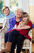 picture of babysitting  - Grandmother with Kids Smiling in the living room - JPG