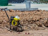 stock photo of vibrator  - Vibrating Plate Machine put on the yellow soil compaction has not quoted - JPG