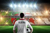 picture of algeria  - Algeria football player holding ball against stadium full of algeria football fans - JPG
