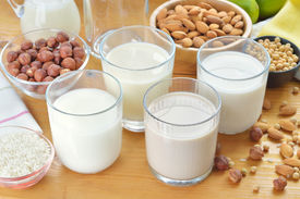 stock photo of substitutes  - Different vegan milks on a table. Hazelnut rice soya and almond milk. Substitute for dairy milk. [[** Note: Shallow depth of field ** Note: Visible grain at 100%, best at smaller sizes - JPG