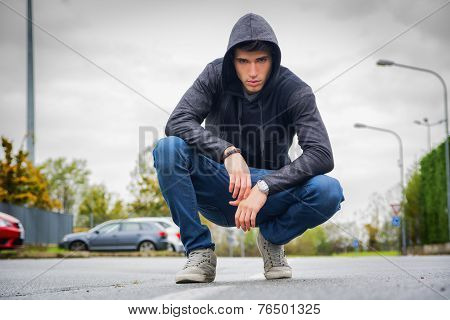 Attractive Young Man With Hoodie And Baseball Cap In City Street