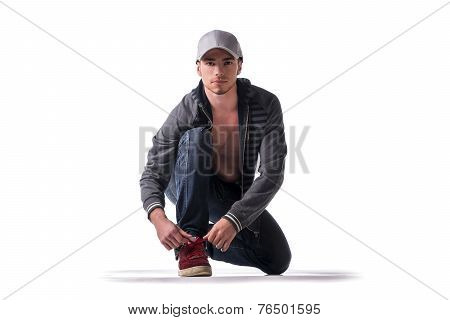Handsome Young Man Kneeling And Tying Sneaker