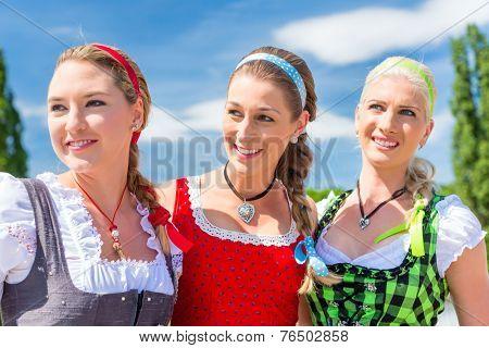 Friends visiting together Bavarian fair in national costume or Dirndl