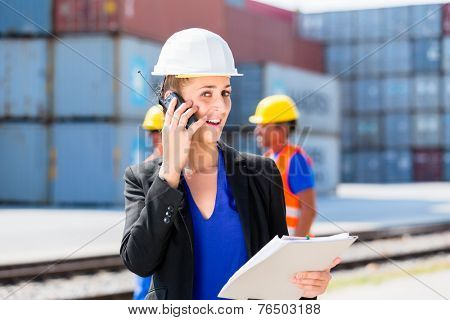 Manager with phone talking on shipment yard in front of container