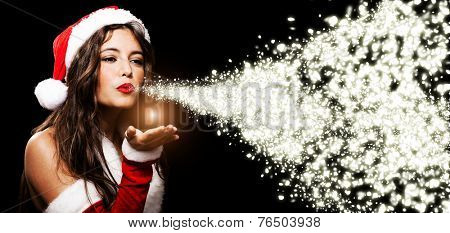 Portrait of a beautiful Christmas girl blowing shining snow flakes