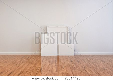3D Rendering of Three blank canvases and frames on a polished wooden parquet floor in an otherwise unfurnished room interior with a white wall ready for your imagination and interior decor