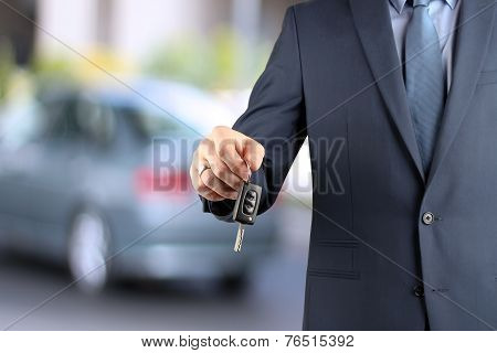 Young Successful Businessman Offering A Car Key. Close-up Of Driver's Hand Showing Key