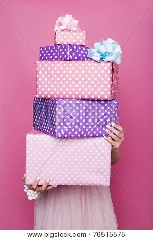 Beautiful woman's hands holding a colorful big and small gift boxes with ribbon. Soft colors.