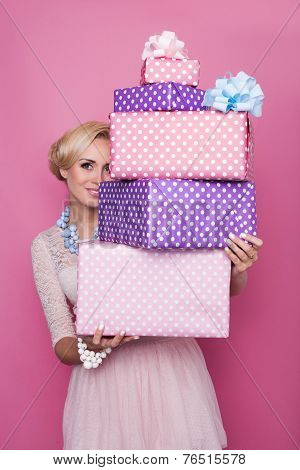 Beautiful blonde woman looking through colorful gift boxes. Soft colors. Christmas, birthday