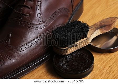 Laced brown leather classic Brogue shoes with polishing cream and brush