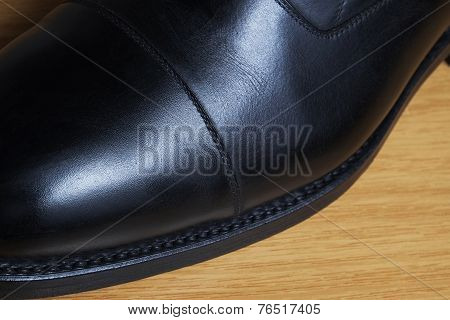 Side view detail of a black leather classic shoe on a wooden dance floor