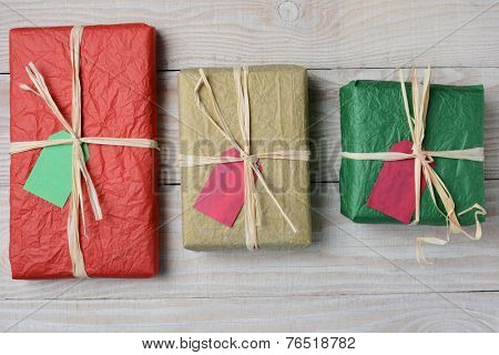 High angle image of three tissue paper wrapped Christmas presents. Horizontal format on a whitewashed rustic wood table.