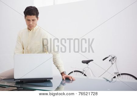 Thoughtful causal businessman using laptop in his office