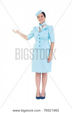 Pretty air hostess showing with hand on white background