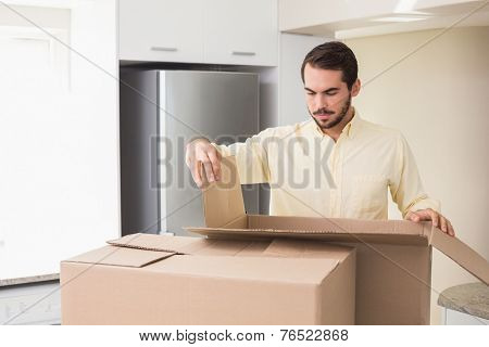 Young man unpacking boxes in kitchen in his new home