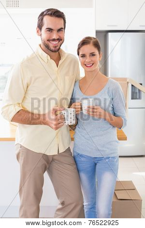 Young couple smiling at the camera in their new home